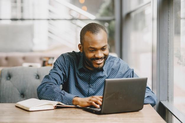 ノートパソコンの後ろで働いて、ノートに書いているアフリカ系アメリカ人の男。カフェに座っているひげを持つ男。