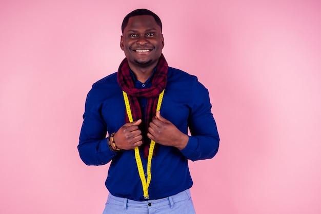 Афро-американский мужчина, работающий в мастерской портной швеи, стильный мужской модельный дизайнер одежды с рулеткой на шее, позирует на розовом фоне в студии
