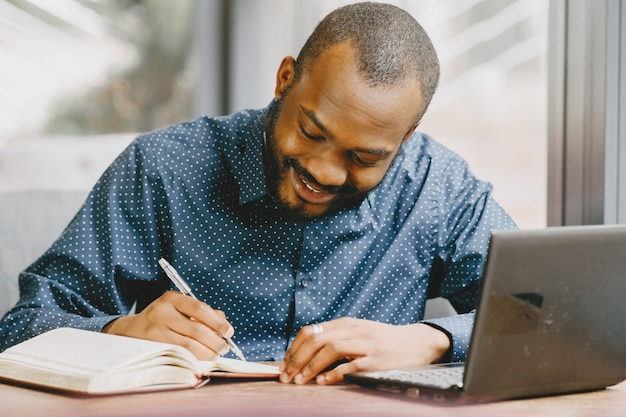 African-american man working behind a laptop and writing in a notebook. man with beard sitting in a cafe.