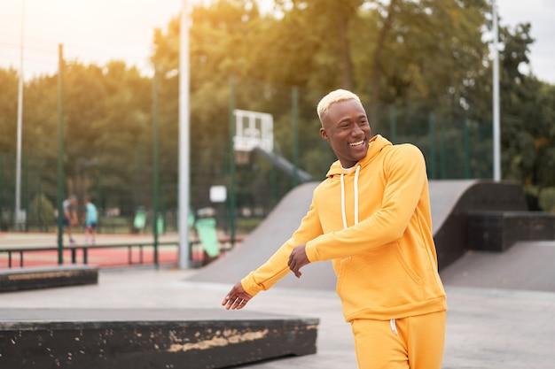 African american man in yellow hoodie outside