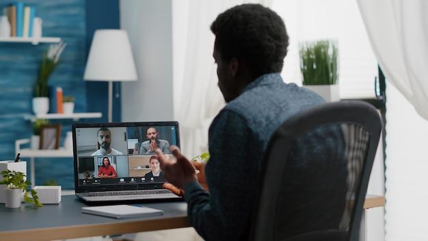 オンラインインターネット会議でアフリカ系アメリカ人のマネージャーが、自宅で仕事をしている同僚とチャットしています...