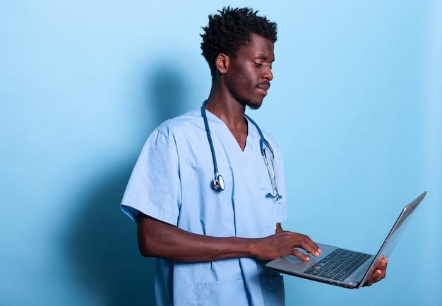 Афро-американский фельдшер, глядя на ноутбук в руке