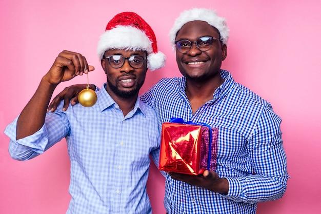Афро-американские мужчины в новогодней шапке с подарочной коробкой на белом фоне. темнокожий санта-клаус с рождеством с мешком, полным рождественских вкусностей, двое друзей празднуют новый год