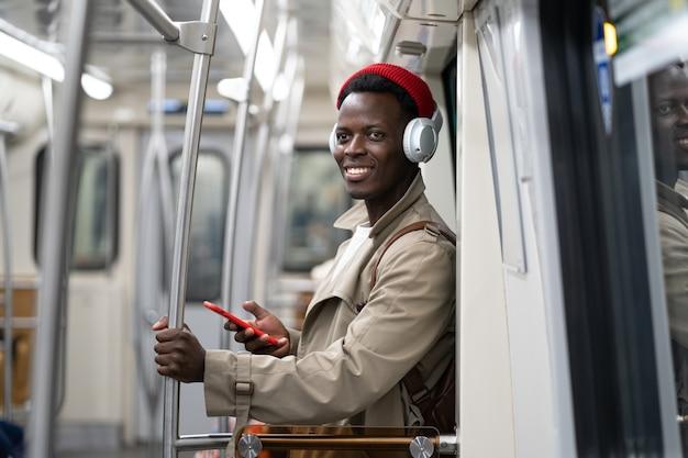 地下鉄の電車の中でアフリカ系アメリカ人のミレニアル世代の男性が携帯電話を使用して、公共交通機関でヘッドフォンで音楽を聴く