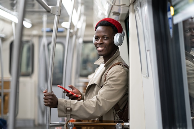 African american millennial man in subway train, using mobile phone, listens to music with headphones in public transportation