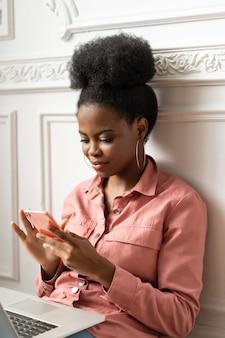 Афро-американская женщина-миллениал с помощью смартфона, набрав сообщение