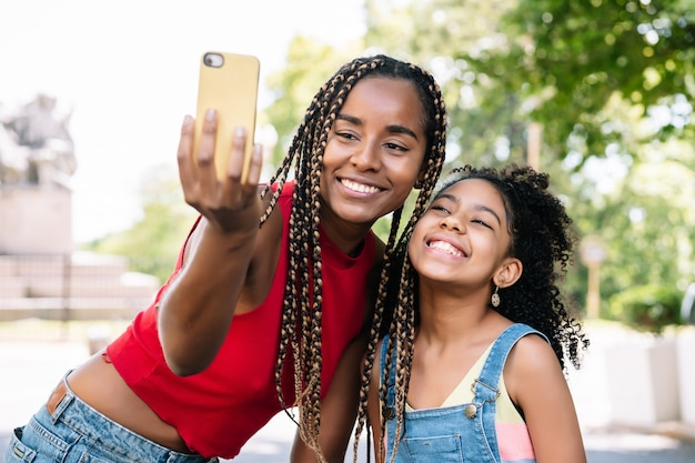 African american mother and daughter enjoying a day outdoors while taking a selfie