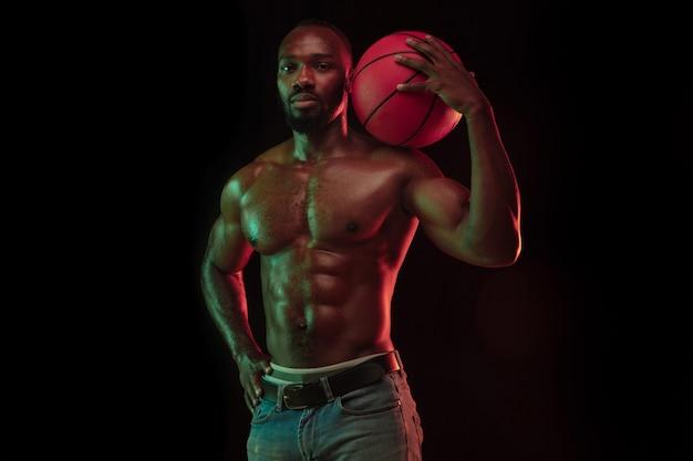 暗いスタジオの背景の上にネオンライトで練習している、ゲームプレイトレーニングのアクションでアフリカ系アメリカ人の筋肉質の若いバスケットボール選手。スポーツ、運動、エネルギー、ダイナミックで健康的なライフスタイルの概念。