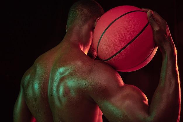 ゲームプレイトレーニングのアクションでアフリカ系アメリカ人の筋肉質の若いバスケットボール選手