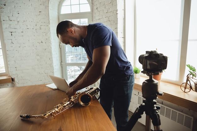 自宅でのオンラインコンサート中にサックスを演奏するアフリカ系アメリカ人のミュージシャンは、隔離され、隔離され、注意を払い、集中しました