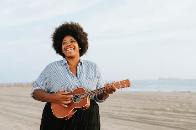アフリカ系アメリカ人の音楽家がビーチでウクレレを演奏