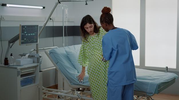 妊娠中の女性を支援するアフリカ系アメリカ人の看護師が病棟のベッドに横たわっていた。医療機器と医療スタッフがいる産科クリニックで赤ちゃんを期待している患者。若い白人の母親