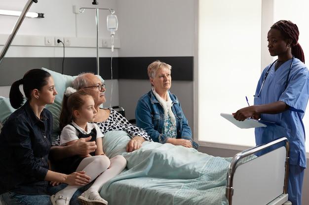 高齢の年配の男性と病気の治療について話し合うアフリカ系アメリカ人の看護師