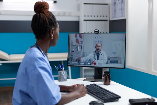 African american nurse explaining sickness symptoms to remote doctor