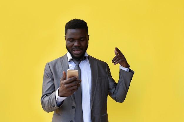 Афроамериканец на желтом фоне с телефоном, выиграл