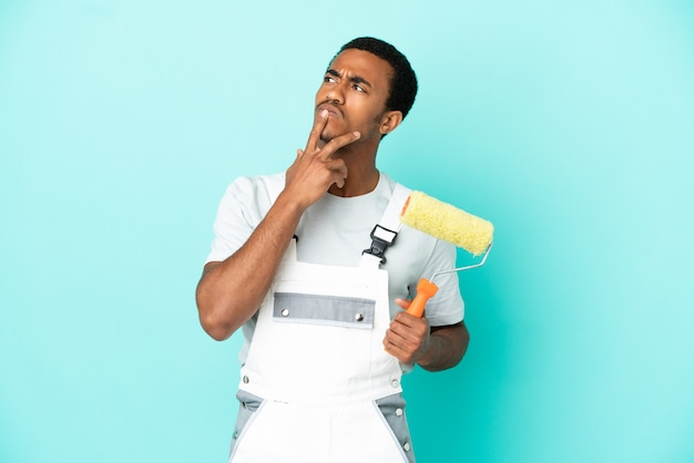 Афро-американский художник человек на изолированном синем фоне, сомневаясь, глядя вверх
