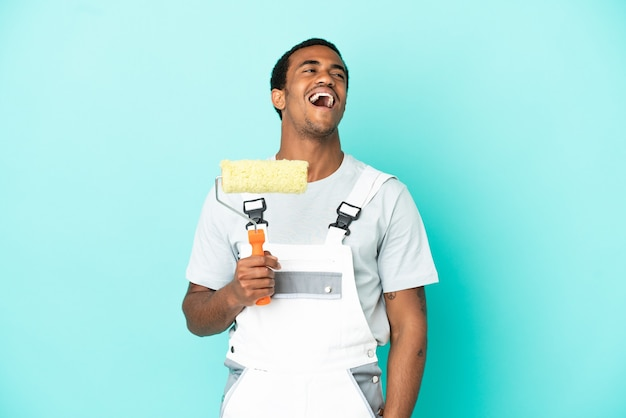 Афро-американский художник человек над изолированным синим фоном смеясь