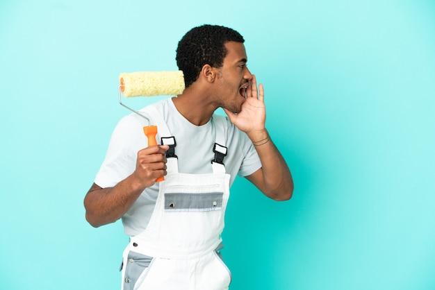 Афро-американский художник человек на изолированном синем фоне кричит с широко открытым ртом в сторону