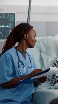 아프리카계 미국인 소아과 간호사가 회복 검사 중에 의료 치료를 작성합니다.