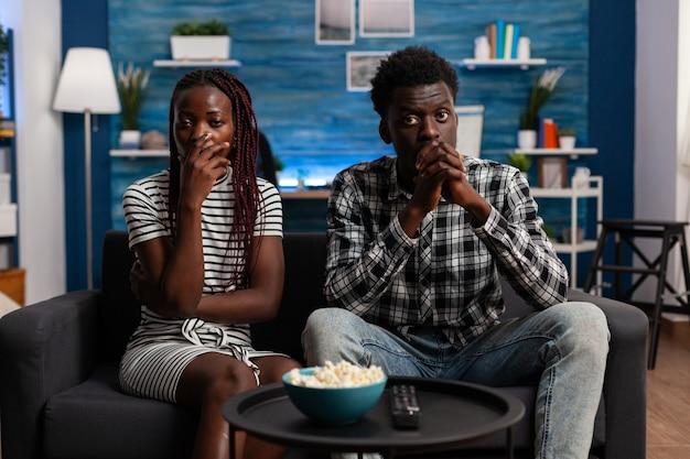 Афро-американцы смотрят драматический фильм по телевизору и находятся в шоке в гостиной. чернокожая женщина и мужчина с рукой над ртом на тв, глядя на камеру. афро пара