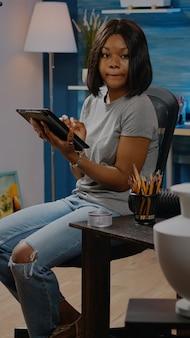 집에 있는 워크샵 스튜디오에서 태블릿을 사용하여 예술적 취미를 가진 아프리카계 미국인. 전문 걸작을 위한 꽃병 그리기 작업을 하는 디지털 기술을 갖춘 흑인 예술가 여성