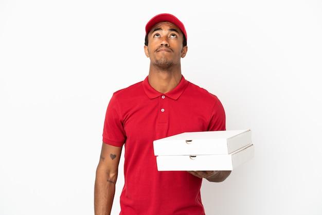 Афро-американский доставщик пиццы собирает коробки для пиццы над изолированной белой стеной и смотрит вверх