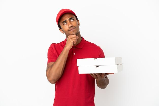 孤立した白い壁の上のピザの箱を拾って見上げるアフリカ系アメリカ人のピザ配達人
