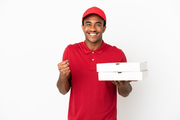 Афро-американский доставщик пиццы собирает коробки для пиццы над изолированной белой стеной, празднуя победу в позиции победителя