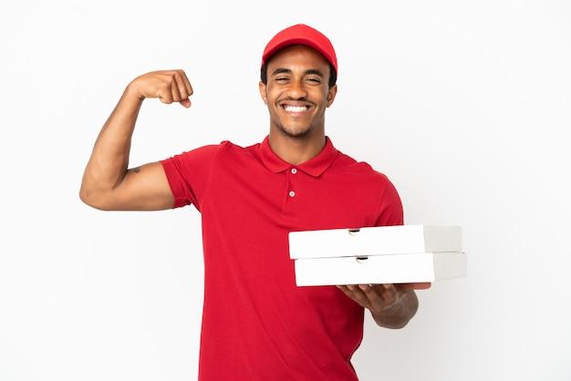 Афро-американский доставщик пиццы собирает коробки для пиццы над изолированной белой стеной, делая сильный жест