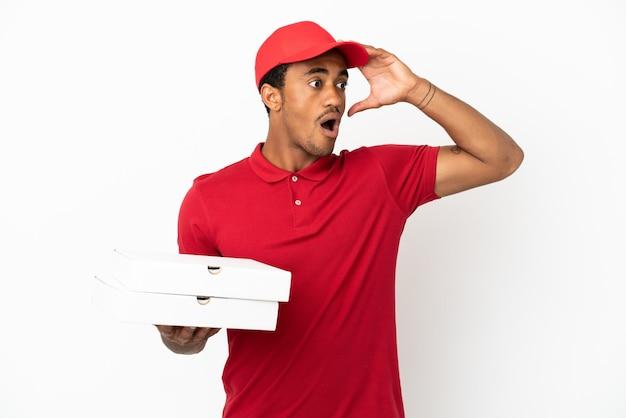 Афро-американский доставщик пиццы собирает коробки для пиццы над изолированной белой стеной, делая неожиданный жест, глядя в сторону