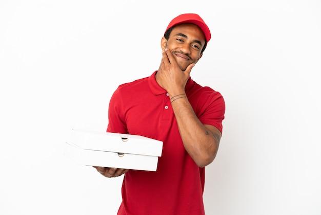 幸せで笑顔の孤立した白い壁の上のピザの箱を拾うアフリカ系アメリカ人のピザ配達人