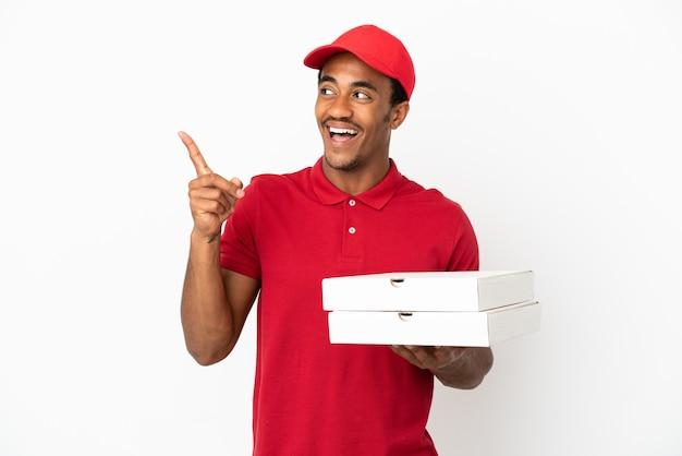 Афро-американский доставщик пиццы поднимает коробки из-под пиццы над изолированной белой стеной, намереваясь реализовать решение, поднимая палец вверх