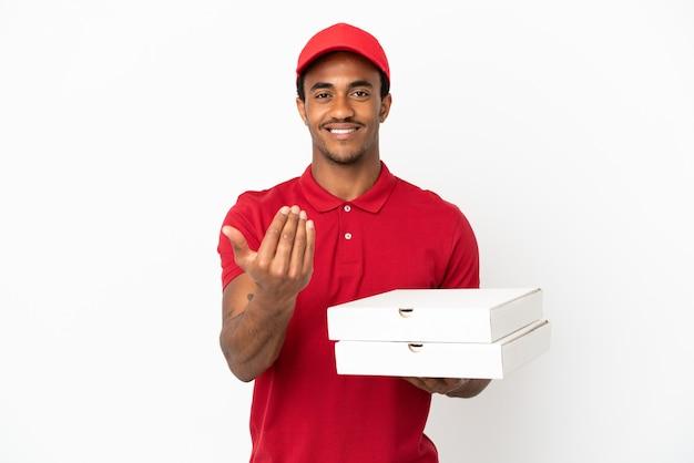 手で来るように誘う孤立した白い壁の上にピザの箱を拾うアフリカ系アメリカ人のピザ配達人。あなたが来て幸せ