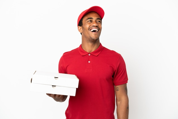 笑っている孤立した白い壁の上のピザの箱を拾うアフリカ系アメリカ人のピザ配達人