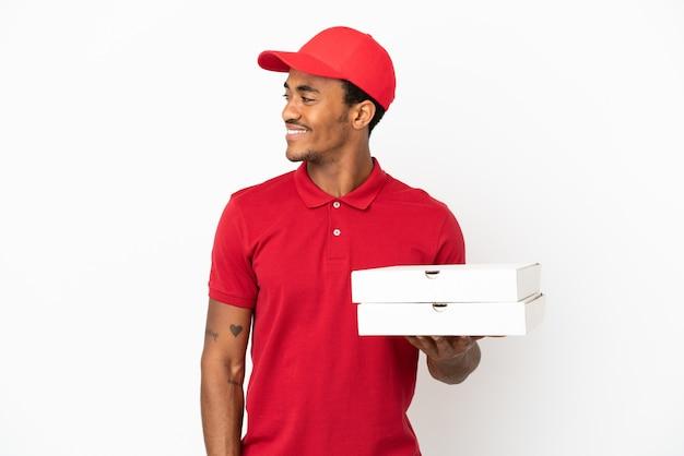 アフリカ系アメリカ人のピザ配達人が横を向いて笑っている孤立した白い壁の上のピザの箱を拾う