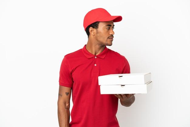 Афро-американский доставщик пиццы собирает коробки для пиццы над изолированной белой стеной, глядя в сторону