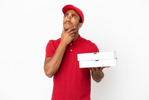 Афро-американский доставщик пиццы собирает коробки для пиццы над изолированной белой стеной, глядя вверх, улыбаясь