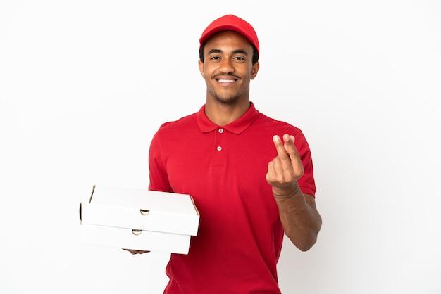 アフリカ系アメリカ人のピザ配達人が孤立した白い壁の上のピザボックスを拾ってお金を稼ぐジェスチャー