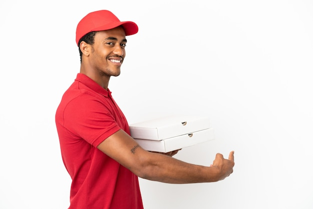 아프리카계 미국인 피자 배달원은 뒤를 가리키는 고립된 흰색 벽 위에 피자 상자를 집어 들고 있다