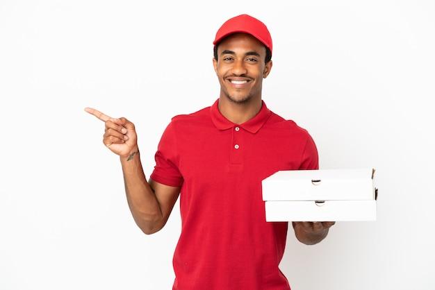 Афро-американский доставщик пиццы собирает коробки для пиццы над изолированной белой стеной, указывая пальцем в сторону