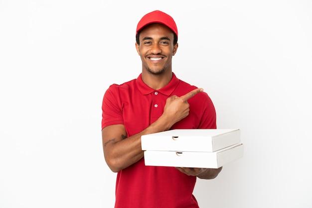 製品を提示するために側面を指している孤立した白い壁の上にピザの箱を拾うアフリカ系アメリカ人のピザ配達人