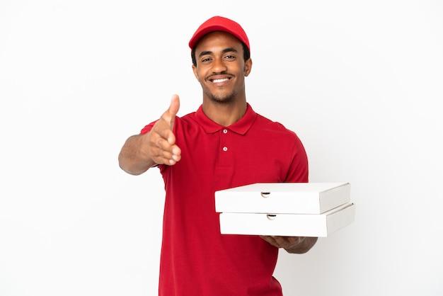 アフリカ系アメリカ人のピザ配達人がかなりの取引を閉じるために握手する孤立した白い壁の上にピザの箱を拾う