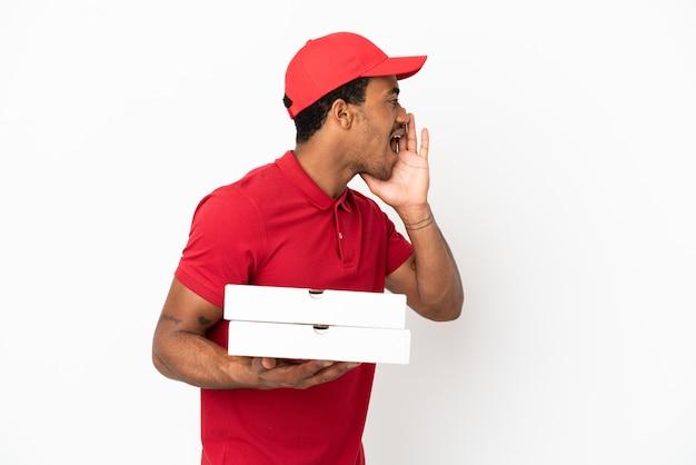 Афро-американский доставщик пиццы собирает коробки для пиццы над изолированной белой стеной и кричит с широко открытым ртом