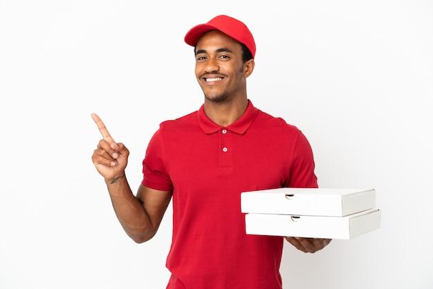 アフリカ系アメリカ人のピザ配達人が孤立した白い壁の上でピザの箱を拾い、最高の兆候を示して指を持ち上げます