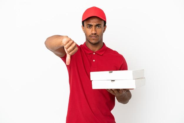 Афро-американский доставщик пиццы собирает коробки для пиццы на изолированной белой стене, показывая большой палец вниз с негативным выражением лица