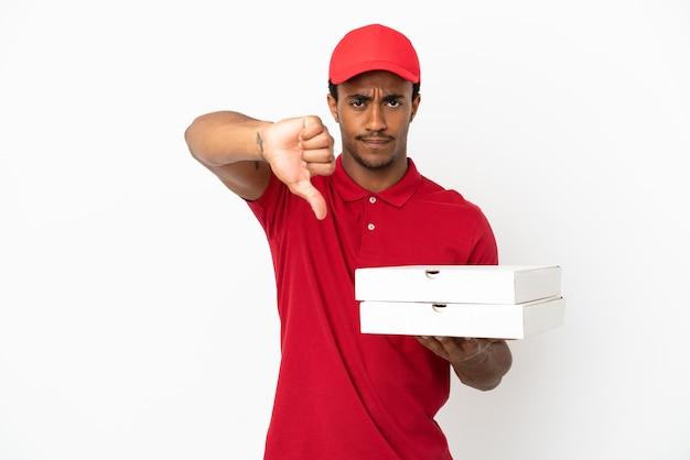 否定的な表現で親指を見せて孤立した白い壁の上のピザの箱を拾うアフリカ系アメリカ人のピザ配達人