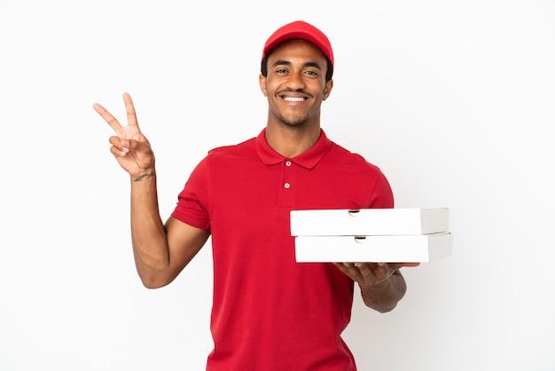 Афро-американский доставщик пиццы собирает коробки для пиццы над изолированной белой стеной, улыбаясь и показывая знак победы