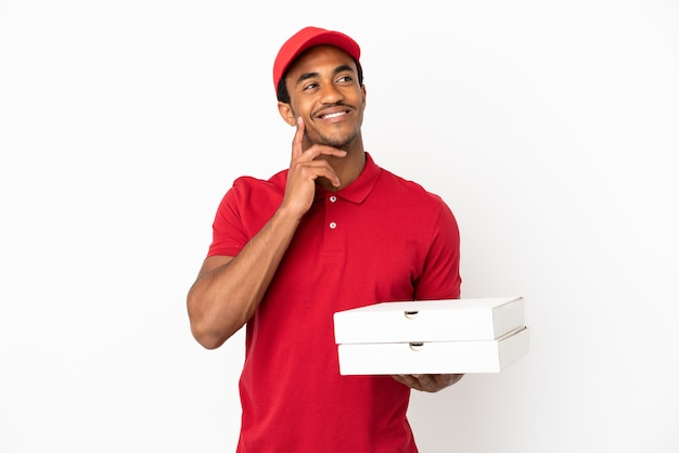 Афро-американский доставщик пиццы собирает коробки для пиццы над изолированной белой стеной, думая об идее, глядя вверх