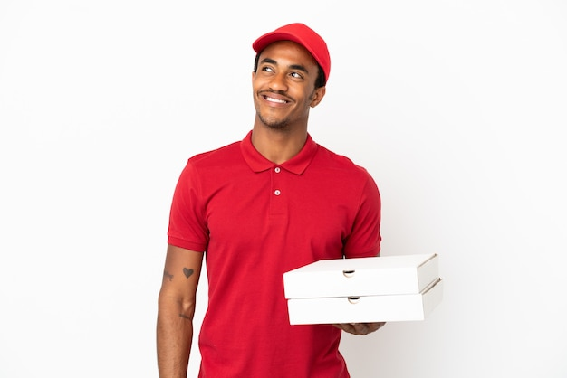 見上げながらアイデアを考えて孤立した白い壁の上のピザの箱を拾うアフリカ系アメリカ人のピザ配達人
