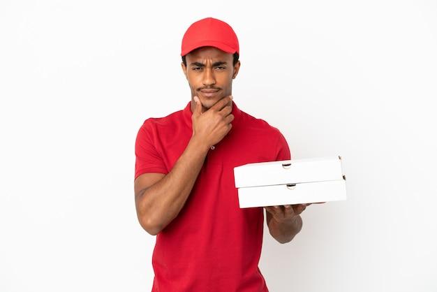 Афро-американский доставщик пиццы собирает коробки для пиццы над изолированной белой стеной, думая